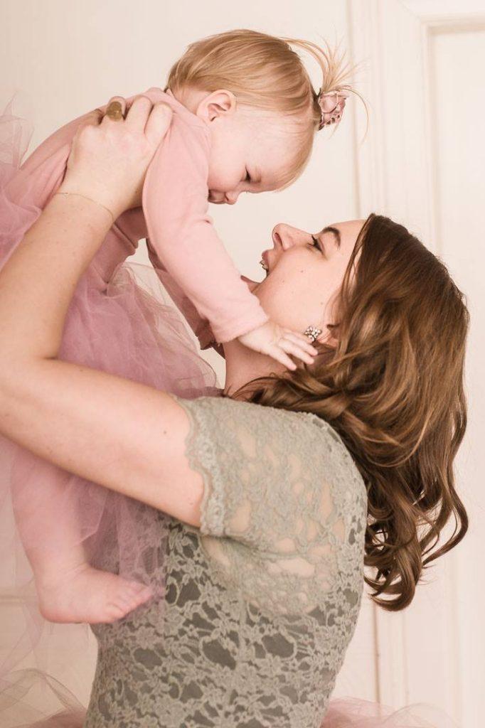 Mor løfter datter op i armene og de griner sammen