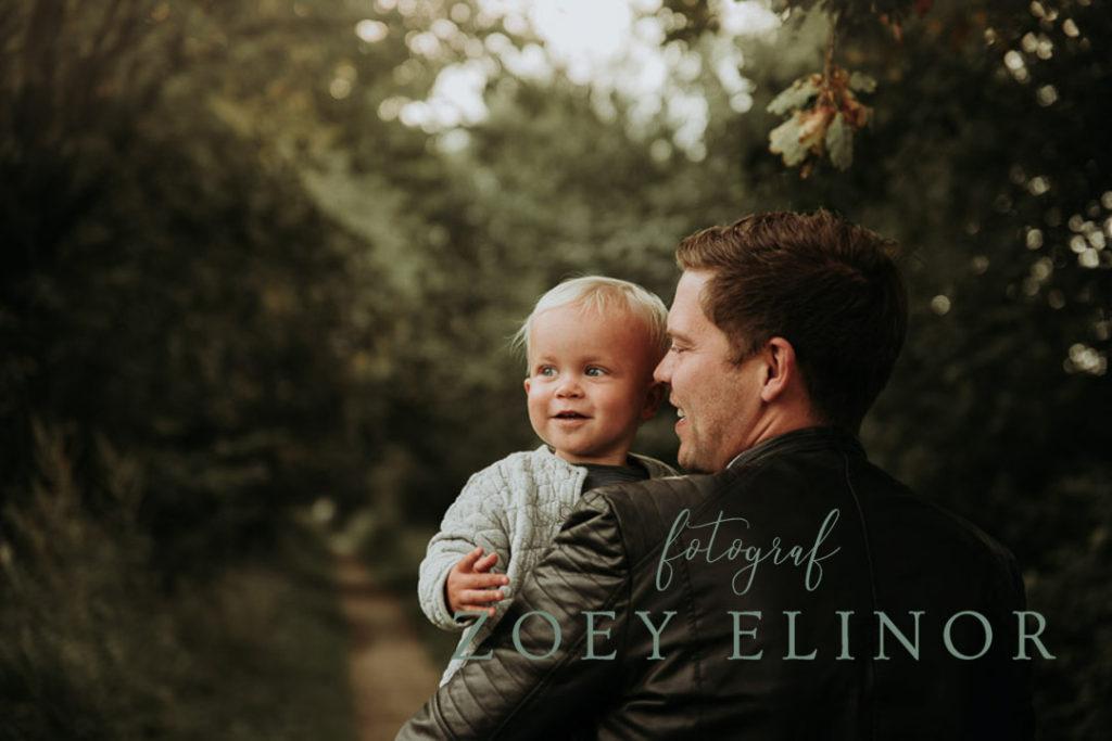 udendørsfotografring, børnefotograf, oppe hos far, smilende dreng, far passer på